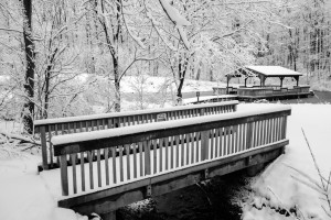 A bridge over the creek covered in snow