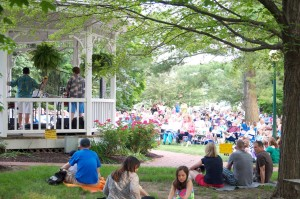 A crowd of people watching a concert under the gazebo