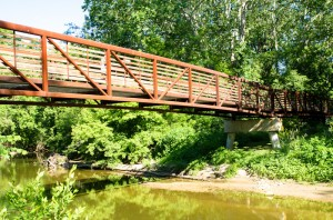 A red, metal bridge over the creek